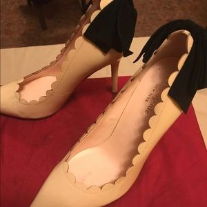 Nude pumps with black bow on heel